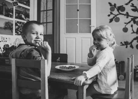 grayscale photo of two kids sitting on dining table chairs